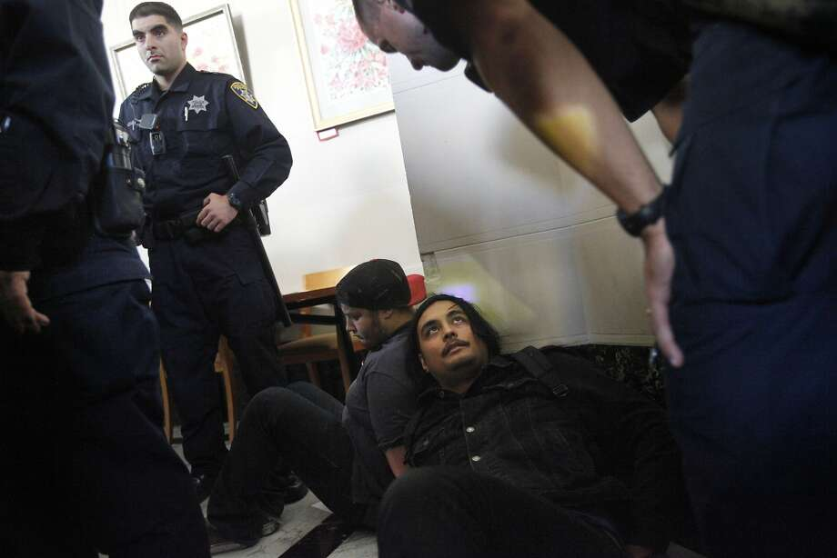 Oakland police officers detain protesters at the raucous Planning Commission meeting. Police said they were not arrested. Photo: Leah Millis, The Chronicle