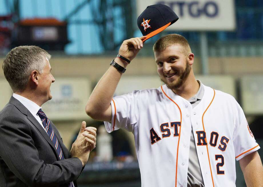 Freshly signed draft pick A.J. Reed shows off his new gear while being introduced Wednesday at Minute Maid Park. Photo: Brett Coomer, Staff / © 2014 Houston Chronicle
