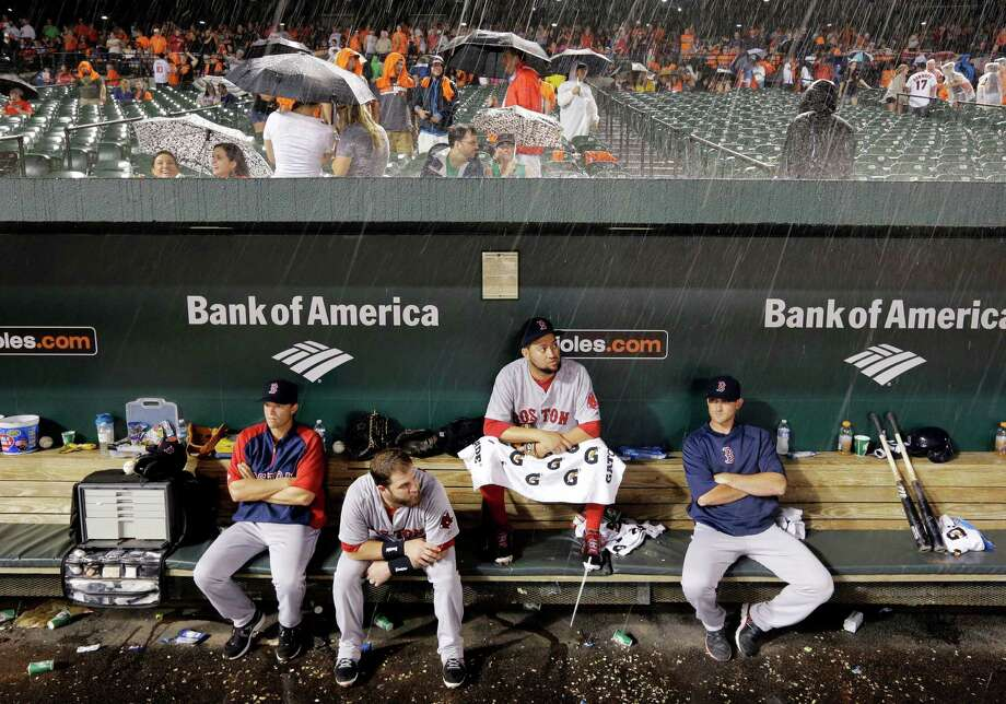 Members of the Boston Red Sox sit in the dugout during a rain delay in a baseball game against the Baltimore Orioles, Wednesday, June 11, 2014, in Baltimore. (AP Photo/Patrick Semansky) ORG XMIT: MDPS114 Photo: Patrick Semansky / AP