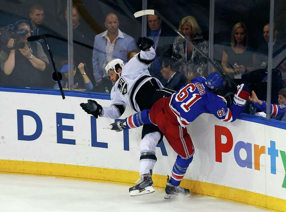 Kings players like Jake Muzzin, left, taking a hit from Rick Nash, found out Wednesday night that the Rangers have plenty of fight left in them. Photo: Jim McIsaac, Stringer / 2014 Getty Images