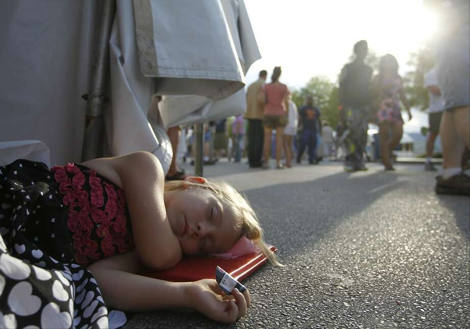 Emily Reed, 5, takes a break during the Riverbend Festival in Chattanooga, Tenn., on Wednesday, June 11, 2014, at the edge of a tent. (AP Photo/Chattanooga Times Free Press, Doug Strickland) Photo: Doug Strickland, Associated Press