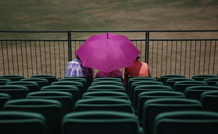 People sit near 18th hole during a practice round for the U.S. Open golf tournament in Pinehurst, N.C., Wednesday, June 11, 2014. The tournament starts Thursday. (AP Photo/David Goldman) Photo: David Goldman, Associated Press