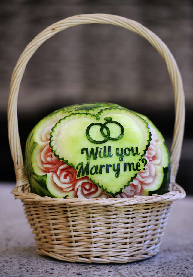 """Will you marry me?"" is carved into a small watermelon at Lesya Griffin's home Tuesday afternoon. Griffin carves intricate designs into fruit for weddings and other special occasions, a skill that she learned on her own. Griffin came to the United States from the Ukraine several years ago. Photo taken Tuesday 6/10/14 Jake Daniels/@JakeD_in_SETX Photo: Jake Daniels / ©2014 The Beaumont Enterprise/Jake Daniels"