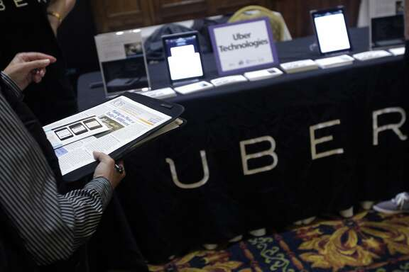 A job seeker talks to recruiters at the Uber table during a mid-Market job fair in San Francisco, Calif. on Tuesday, June 10, 2014. The popular ridesharing service is seeking as many qualified drivers they can find.