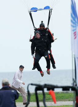 Former President George H.W. Bush, strapped to Sgt. 1st Class Mike Elliott, a retired member of the Army's Golden Knights parachute team, prepare to land on the lawn at St. Anne's Episcopal Church while celebrating Bush's 90th birthday in Kennebunkport, Maine, Thursday, June 12, 2014. (AP Photo/Robert F. Bukaty) Photo: Robert F. Bukaty, Associated Press / AP