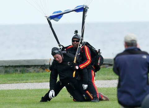 Former President George H.W. Bush, left, strapped to Sgt. 1st Class Mike Elliott, a retired member of the Army's Golden Knights parachute team, land on the lawn at St. Anne's Episcopal Church after making a tandem parachute jump near Bush's summer home in Kennebunkport, Maine, Thursday, June 12, 2014. Bush made the jump, his eighth, in celebration of his 90th birthday. (AP Photo/Robert F. Bukaty) Photo: Robert F. Bukaty, Associated Press / AP