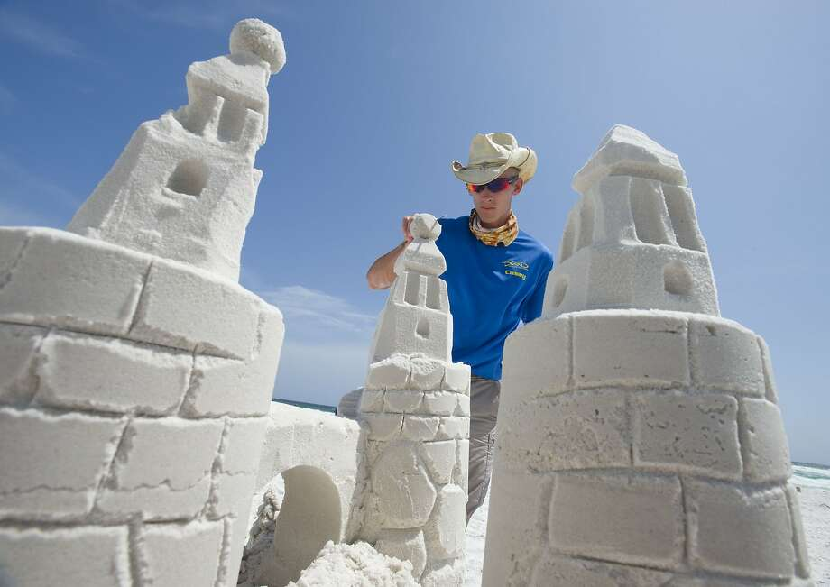 Making the moats of your Florida vacation: Casey Fabianski of Beach Sand Sculptures puts the finishing touches on a castle at the beach in Destin, Fla. Fabianski was giving sand castle-building lessons to tourists. Photo: Devon Ravine, Associated Press