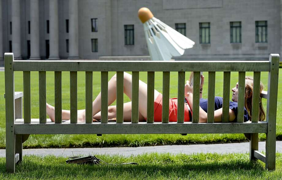 Big birdie:Elementary school teacher Liz Cox reads outside the Nelson-Atkins Museum of Art in Kansas City, Mo., where they play the world's biggest badminton matches. Photo: Fred Blocher, Associated Press