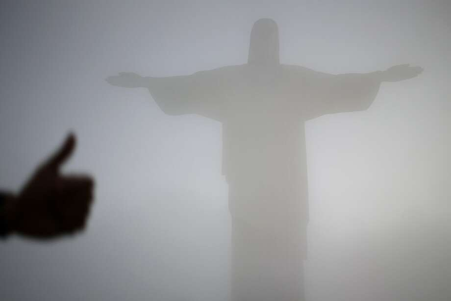 Hey J.C., J.C., you're alright by me: A tourist gives the thumbs-up to Jesus at a fog-shrouded Christ the Redeemer statue in Rio de Janeiro. Photo: Hassan Ammar, Associated Press