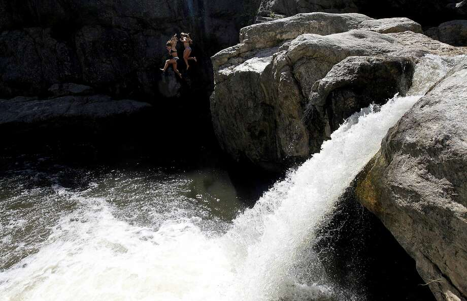 Hippie dippy: Sarah Houghland, 15, and Hannah Wang, 16, jump off a cliff and into the cool water of Hippie Hole, a popular swimming spot on Battle Creek near Rapid City, S.D. Photo: Chris Huber, Associated Press