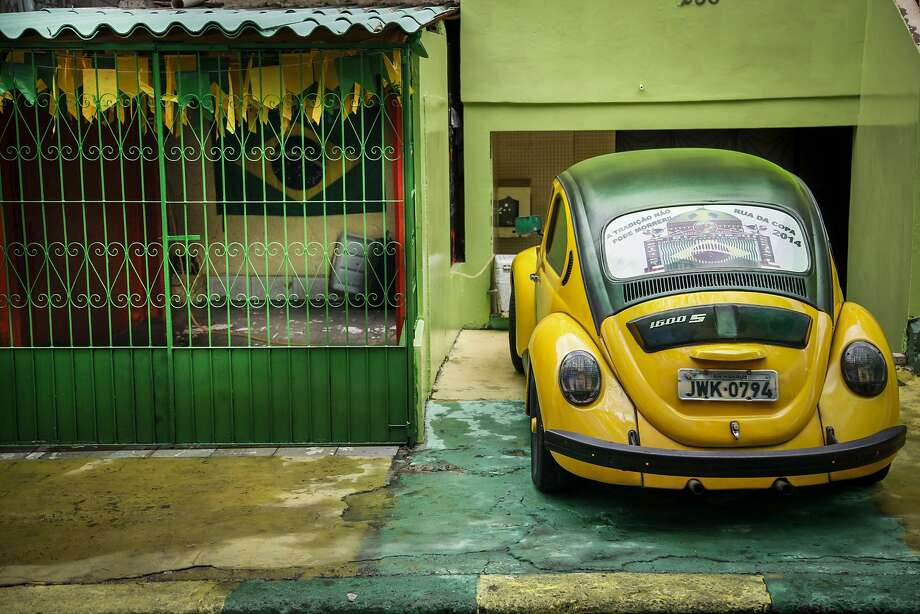 That home team spirit:A football fan in the Rio de Janeiro neighborhood of Manaus painted his Beetle in Brazil's colors to match his green-and-yellow house, so it's a good bet he won't be missing any of Brazil's World Cup games. Photo: Raphael Alves, AFP/Getty Images