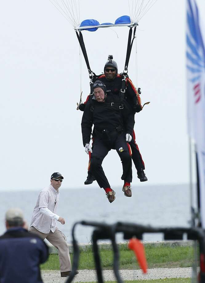 Bush 41 turns 90, takes the plunge:Former President George H.W. Bush, strapped to Sgt. 1st Class Mike Elliott, lands on the lawn at St. Anne's Episcopal Church in Kennebunkport, Maine. Bush celebrated his 90th birthday with a tandem skydive. Photo: Robert F. Bukaty, Associated Press