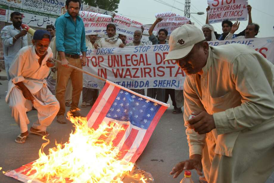 Pakistani demonstrators burn a US flag during a protest against a US drone strike in Multan on June 12, 2014. Pakistan on June 12 condemned the first US drone strikes on its soil this year despite suspicions the two countries coordinated over the attack in the aftermath of a Taliban siege of Karachi airport. AFP PHOTO/S S MIRZAS S MIRZA/AFP/Getty Images Photo: S S Mirza, AFP/Getty Images