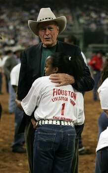 Calf Scramble contestant Brittany Marsh of Houston hugs former President George Bush after the calf scramble in the first performance of the 2006 Houston Livestock Show and Rodeo. Photo: James Nielsen, Freelance / Freelance