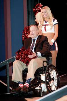 George H.W. Bush being assisted by a Texans cheerleader at the Celebration of Reading in 2013. Photo: Courtesy Barbara Bush Foundation