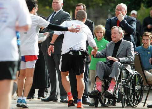 Former President George H. W. Bush shakes hands with runners during the Chevron Houston Marathon on Sunday, Jan. 15, 2012 Photo: Mayra Beltran, Staff / © 2011 Houston Chronicle