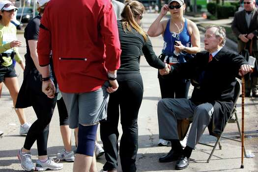 Runners stop to greet former President George H. W. Bush around mile 19  during the Chevron Houston Marathon in 2010. Photo: Melissa Phillip, Staff / Houston Chronicle