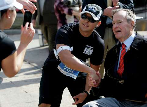 Vincent Luan of Houston stops during his run to have his photo taken with former President George H. W. Bush during the 2010 Chevron Houston Marathon Photo: Melissa Phillip, Staff / Houston Chronicle