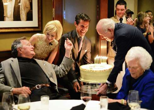More than 100 friends and family members - and the Texas A&M Singing Cadets - gathered at the Palm Restaurant in April for an early celebration of former President George H.W. Bush's 90th birthday. Milton Townsend, left, and Jackson Hicks bring a large carrot cake to the table shared by Barbara Bush. Photo: Al Torres Photography / AL TORRES         PHOTOGRAPHY