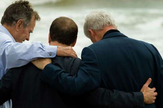 Former U.S. Presidents George H.W. Bush and Bill Clinton stand arm-in-arm with local business leader Tilman Fertitta at Bermuda Beach as they tour areas affected by Hurricane Ike  in Galveston. The two former presidents have created the Bush-Clinton Coastal Recovery Fund to focus on long-term recovery efforts all along the Gulf coast. Photo: Smiley N. Pool, Staff / Houston Chronicle