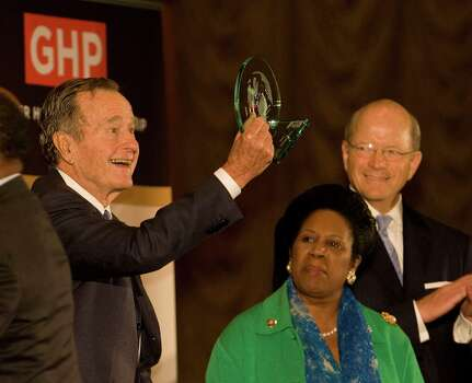 "President George H.W. Bush (left) holds up a glass art piece titled ""Light Spikes"" commerating the 40th anniversary of Bush International Airport by artist Jay Baker Photo: James Nielsen, Staff / Houston Chronicle"