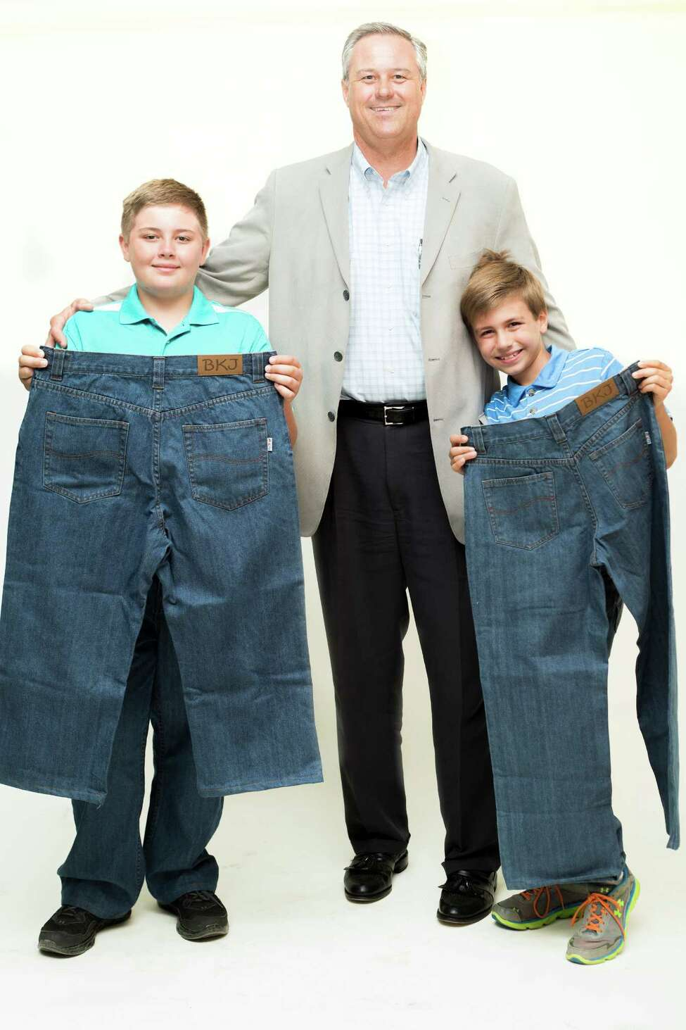 Alec, 11, left, and his brother, Kyle, 9, right, stand with their father and founder of Big Kidz Jeanz, Steve, as they display Big Kidz Jeans on Thursday, June 6, 2014 in Albany, N.Y. Steve Frazee is the founder of Big Kidz Jeanz, a company he started because he had a hard time finding pants to fit his