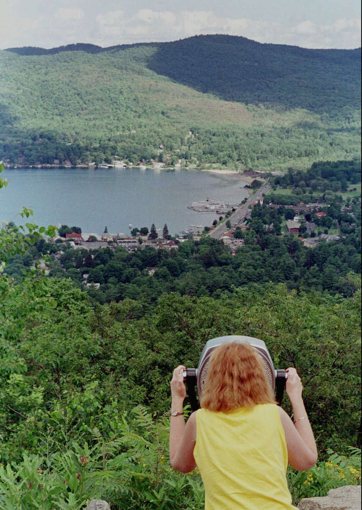 A woman views the southern end of Lake George and the village of Lake George, N.Y., from Prospect Mountain Parkway July 2, 1998. The summit is reopening on Sept. 5, 2020, with pandemic restrictions in place, including the removal of the view scopes. (AP Photo/Jim McKnight)