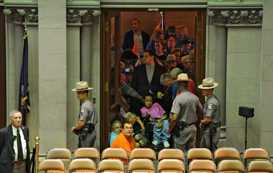 A group advocating to expand the range of home care options for the disabled, block a doorway to the Assembly Chamber Wednesday, June 11, 2014, at the Capitol in Albany, N.Y. (Lori Van Buren / Times Union) Photo: Lori Van Buren, Albany Times Union
