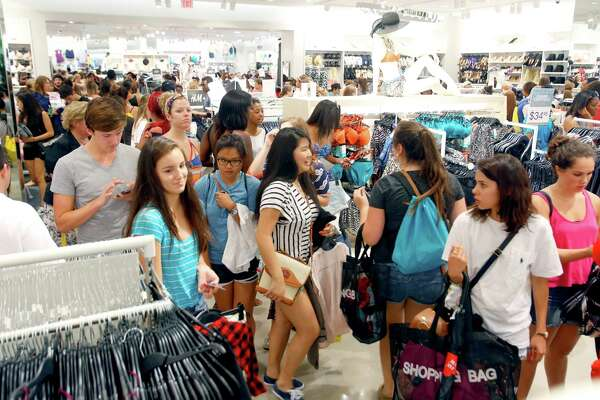 Some of the over 1,100 people who lined up for H&M clothing store's grand opening Thursday morning June 12, 2014 shop inside the store at the Shops at La Cantera.