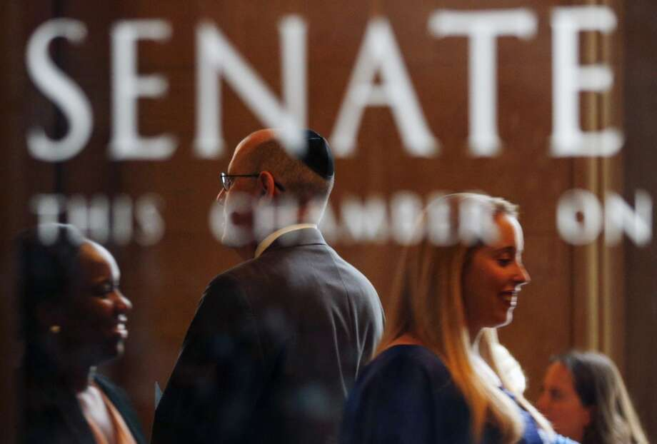 People stand in the lobby of the Senate Chamber as legislators work in the final two weeks of the legislative session on Tuesday, June 10, 2014, in Albany, N.Y. (AP Photo/Mike Groll) ORG XMIT: NYMG101 Photo: Mike Groll, AP