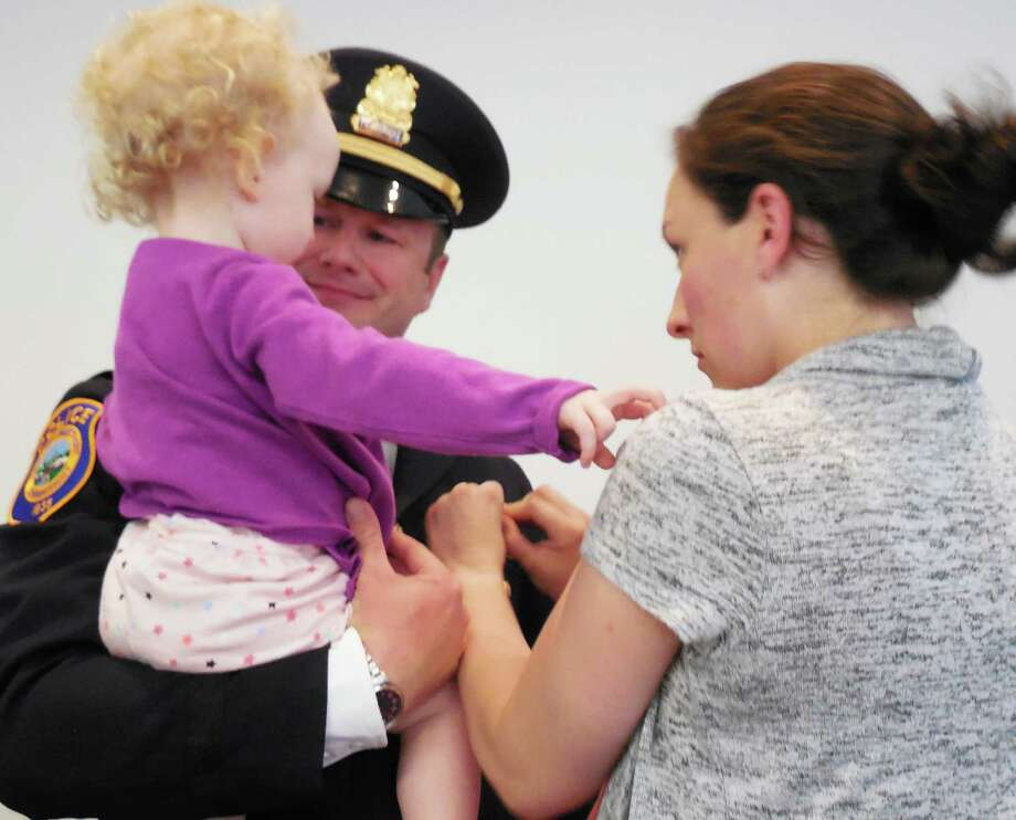 Ryan Paulsson was promoted to the rank of lieutenant. With him are his wife, Jacqui, and daughter, Emmalyn, following his swearing in Thursday afternoon at Police Headquarters. Photo: Anne M. Amato / westport news