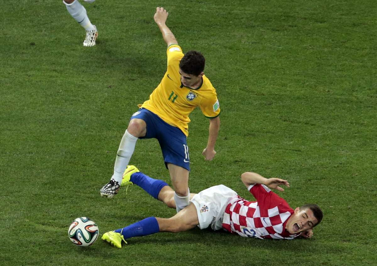 Brazil's Oscar, left, and Croatia's Mateo Kovacic, challenge for the ball during the group A World Cup soccer match between Brazil and Croatia, the opening game of the tournament, in the Itaquerao Stadium in Sao Paulo, Brazil, Thursday, June 12, 2014.