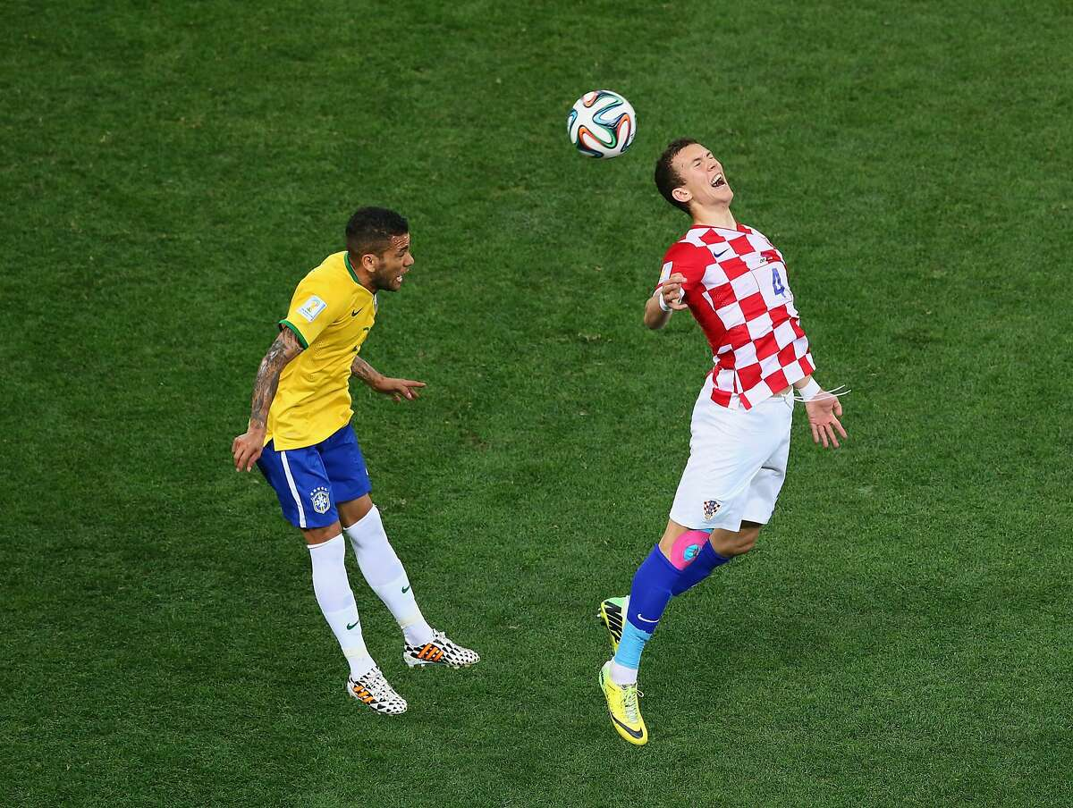 Ivan Perisic of Croatia goes up for a header against Dani Alves of Brazil during the 2014 FIFA World Cup Brazil Group A match between Brazil and Croatia at Arena de Sao Paulo on June 12, 2014 in Sao Paulo, Brazil.