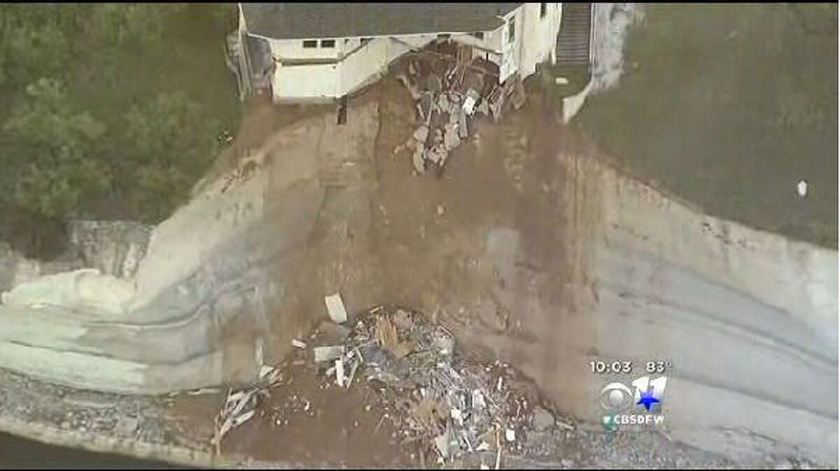 A luxury house teeters on a cliff about 75 feet above Lake Whitney in Whitney, Texas, as seen from CBS Dallas footage. WFAA-TV reported Wednesday, June 11, 2014 that the house had been condemned and the owners evacuated about two weeks earlier.