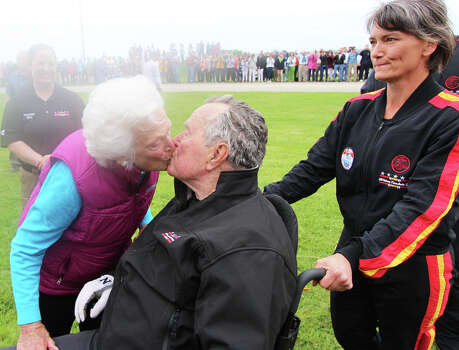 In this photo provided by the All Veteran Parachute Team, Barbara Bush kisses former President George H.W. Bush after his landing of a parachute jump on his 90th birthday in Kennebunkport, Maine, Thursday, June 12, 2014. (AP Photo/All Veteran Parachute Team, Kenneth Wasley) Photo: Kenneth Wasley, Associated Press / All Veteran Parachute Team