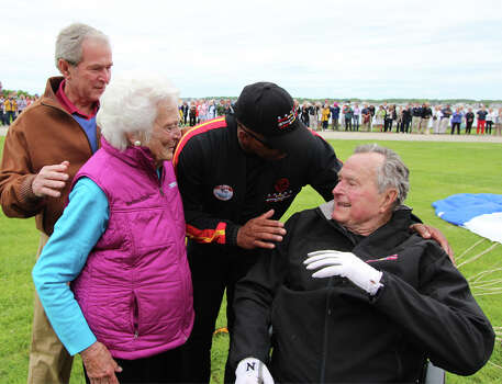 In this photo provided by the All Veteran Parachute Team, former President George H.W. Bush, right, is congratulated on his parachute jump by his son, former President George W. Bush, far left, his wife Barbara Bush and his tandem team partner Mike Elliott on his 90th birthday in Kennebunkport, Maine, Thursday, June 12, 2014. (AP Photo/All Veteran Parachute Team, Kenneth Wasley) Photo: Kenneth Wasley, Associated Press / All Veteran Parachute Team