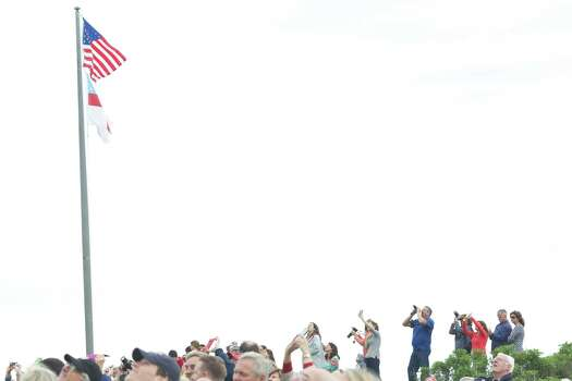 Spectators watch as former U.S. President George H.W. Bush and Mike Elliott, US Army Sergeant 1st Class (ret), jump out of a helicopter and parachute down to St. Anne's Episcopal Church on June 12, 2014 in Kennebunkport, Maine. The President is celebrating his 90th birthday today. Photo: Eric Shea, Getty Images / 2014 Getty Images