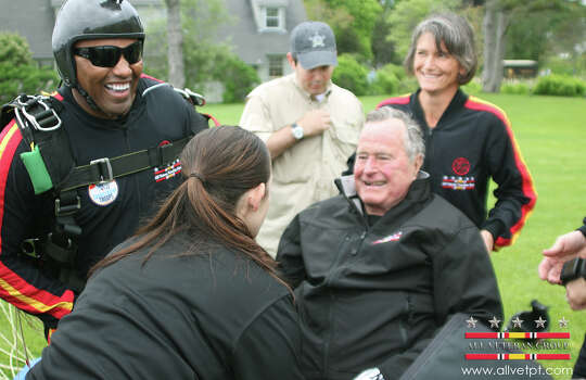 In this photo provided by the All Veteran Parachute Team, former President George H.W. Bush is checked by a doctor with the All Veteran Parachute Team after his landing of a parachute jump on his 90th birthday in Kennebunkport, Maine, Thursday, June 12, 2014. (AP Photo/All Veteran Parachute Team, Kenneth Wasley) Photo: Kenneth Wasley, Associated Press / All Veteran Parachute Team