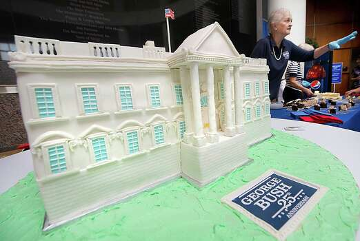 A White House-shaped birhtday cake rests on a table as George Bush Presidential Library and Museum docent Sandra Wood passes out free slices of cake at the museum's celebration of Bush's 90th birthday in College Station, Texas,  Thursday, June 12, 2014.  Visitors to the museum were encouraged to wear their craziest pair of socks in honor of the 41st president, who routinely wears colorful socks.  (AP Photo/Bryan-College Station Eagle, Stuart Villanueva) Photo: Stuart Villanueva, MBR / Bryan College Station Eagle