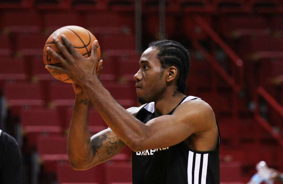 Kawhi Leonard's hand measures 9.75 inches long, larger than the diameter of an NBA basketball.  Photo: Kin Man Hui, San Antonio Express-News / ©2014 San Antonio Express-News