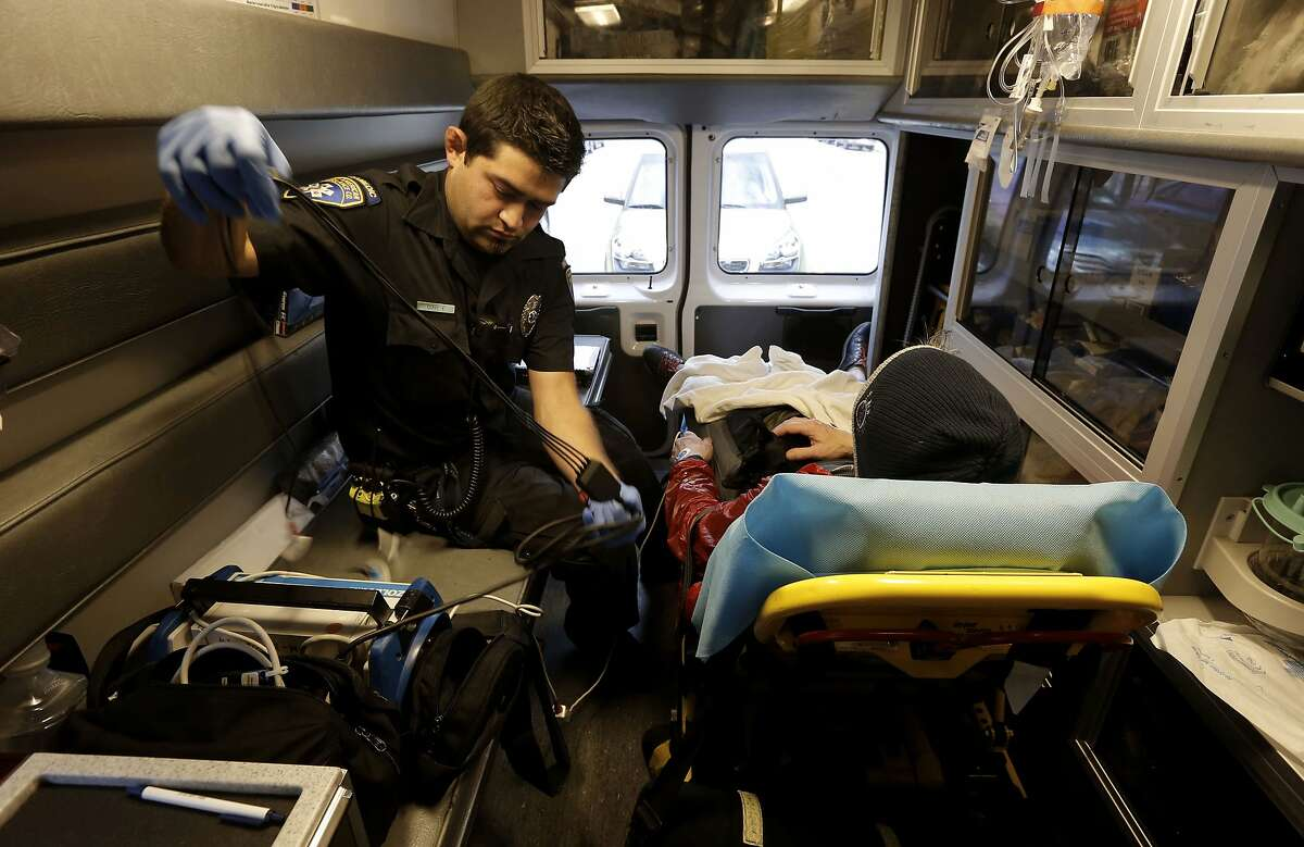 Paramedic Cory Yeo, with the King-American Ambulance tends to an assault victim during a transport to UCSF medical center, on Thursday 12, 2014, in San Francisco, Calif. A report by the budget analyst reports the city needs to increase its ambulance staffing, improve its emergency system coordination and 911 dispatch system and replace it's aging ambulance fleet.