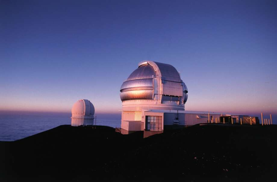 The 8-meter Gemini Telescope (foreground), seen at sunrise, is one of 13 on the summit of Mauna Kea on the island of Hawaii.  A group of Native Hawaiian activists is  seeking to block the proposed Thirty Meter Telescope  (TMT), which would cover an 8-acre area on the mountain, citing cultural and environmental concerns. Photo: Kirk Lee Aeder,  Hawaii Tourism Authority (HTA)