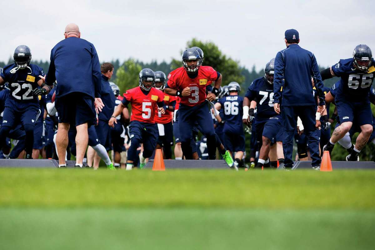 Seahawks quarterback Russell Wilson, center, joins other players to run drills on the ninth and final day of Organized Team Activities Thursday, June 12, 2014, at the Virginia Mason Athletic Center in Renton, Wash.