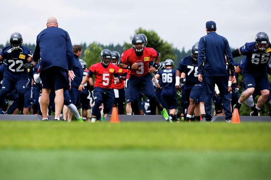 Seahawks quarterback Russell Wilson, center, joins other players to run drills on the ninth and final day of Organized Team Activities Thursday, June 12, 2014, at the Virginia Mason Athletic Center in Renton, Wash. Photo: JORDAN STEAD, SEATTLEPI.COM / SEATTLEPI.COM