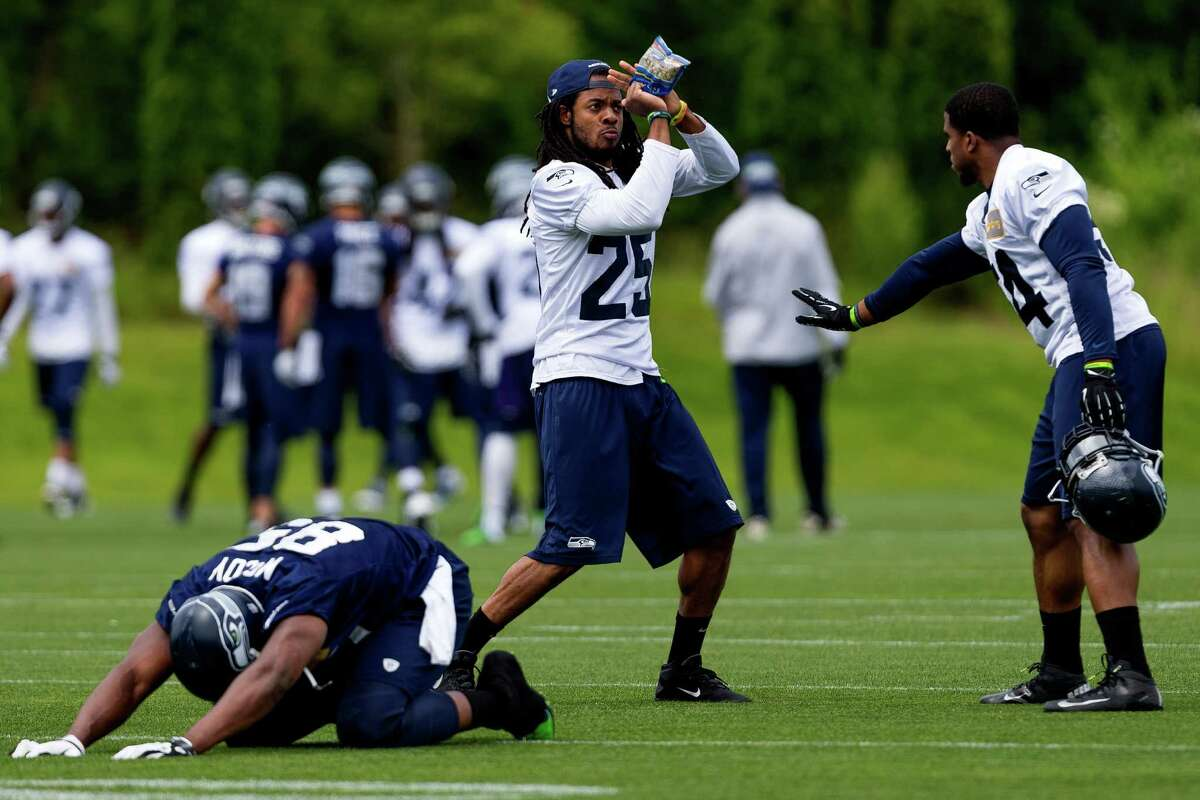 Seahawks players Richard Sherman, center, and Bobby Wagner, right, goof around between drills on the ninth and final day of Organized Team Activities Thursday, June 12, 2014, at the Virginia Mason Athletic Center in Renton, Wash.