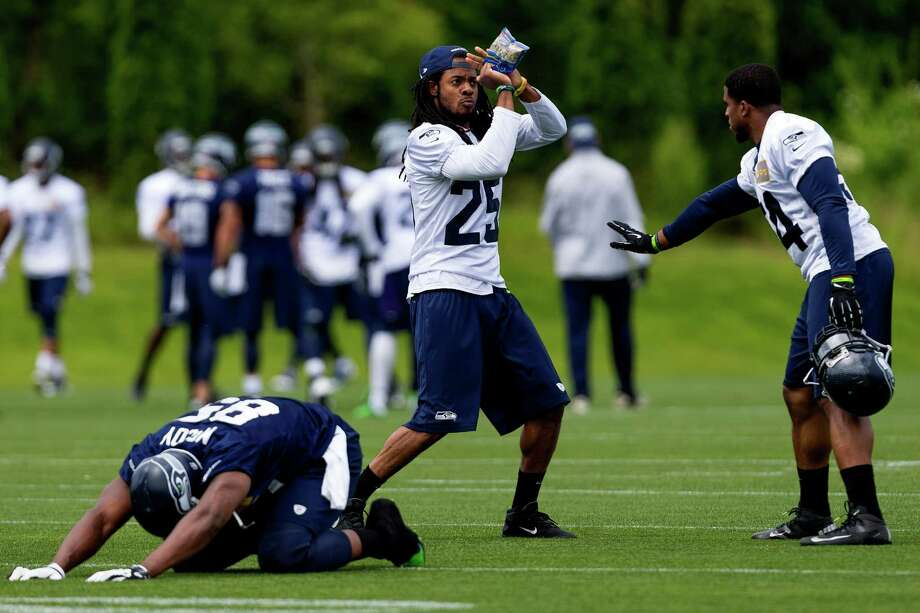Seahawks players Richard Sherman, center, and Bobby Wagner, right, goof around between drills on the ninth and final day of Organized Team Activities Thursday, June 12, 2014, at the Virginia Mason Athletic Center in Renton, Wash. Photo: JORDAN STEAD, SEATTLEPI.COM / SEATTLEPI.COM