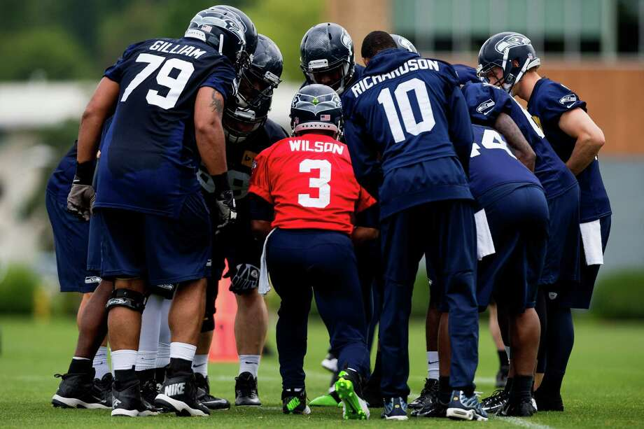 Seahawks players huddle up with quarterback Russell Wilson, center, on the ninth and final day of Organized Team Activities Thursday, June 12, 2014, at the Virginia Mason Athletic Center in Renton, Wash. Photo: JORDAN STEAD, SEATTLEPI.COM / SEATTLEPI.COM