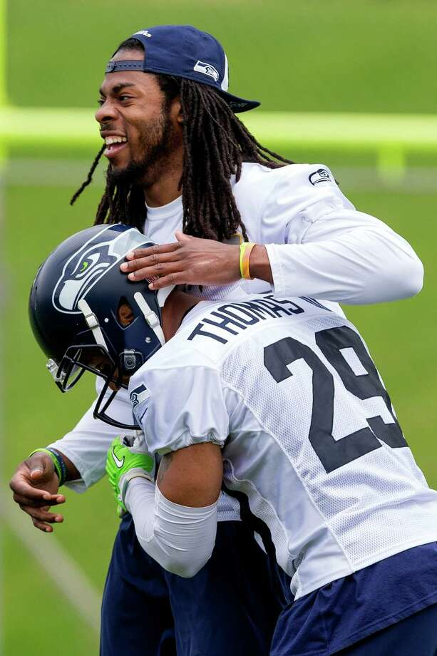 Seahawks player Richard Sherman, top, laughs and hugs teammate Earl Thomas, bottom, on the ninth and final day of Organized Team Activities Thursday, June 12, 2014, at the Virginia Mason Athletic Center in Renton, Wash. Photo: JORDAN STEAD, SEATTLEPI.COM / SEATTLEPI.COM
