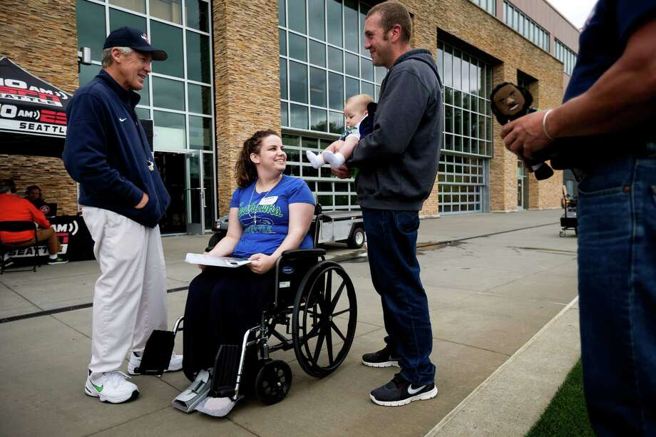 Seahawks' head coach Pete Carroll, left, meets with Oso mudslide survivors Amanda Skorjanc, center, baby Duke Suddarth, center, and fiancŽ Ty Suddarth , center right, following the ninth and final day of Organized Team Activities Thursday, June 12, 2014, at the Virginia Mason Athletic Center in Renton, Wash. Photo: JORDAN STEAD, SEATTLEPI.COM / SEATTLEPI.COM
