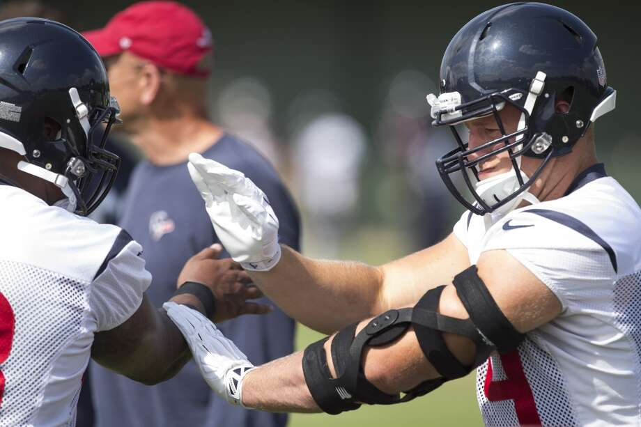 Defensive end J.J. Watt, right, runs a drill with Keith Browner. Photo: Brett Coomer, Houston Chronicle